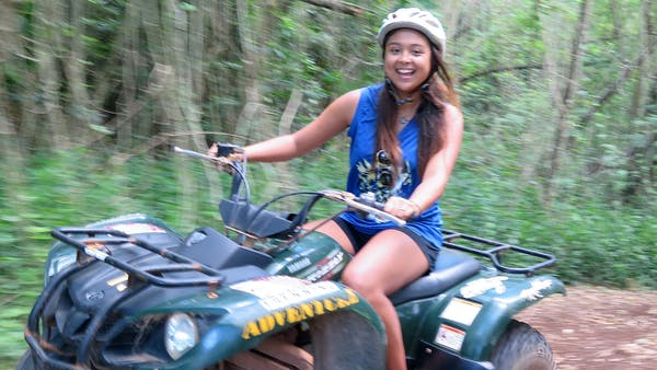 A young woman driving her ATV