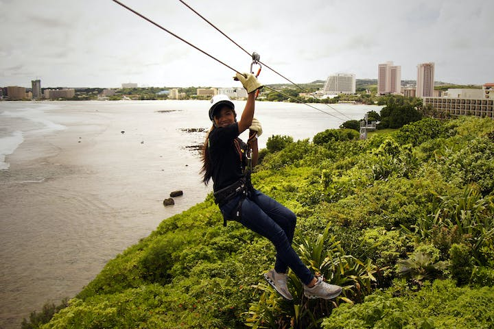 A woman ziplining across to the base