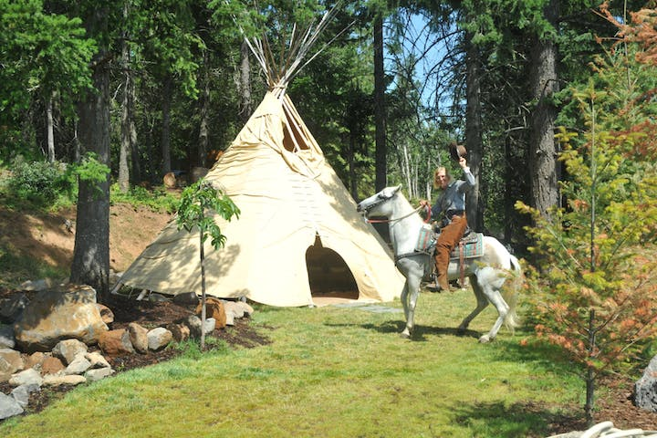 Woman on horse next to TeePee