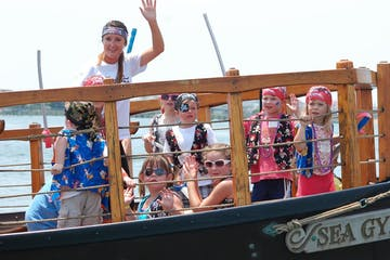 A group waving at the camera from a boat