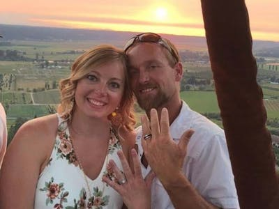 Couple showing their engagement rings on the sunset hot air balloon ride