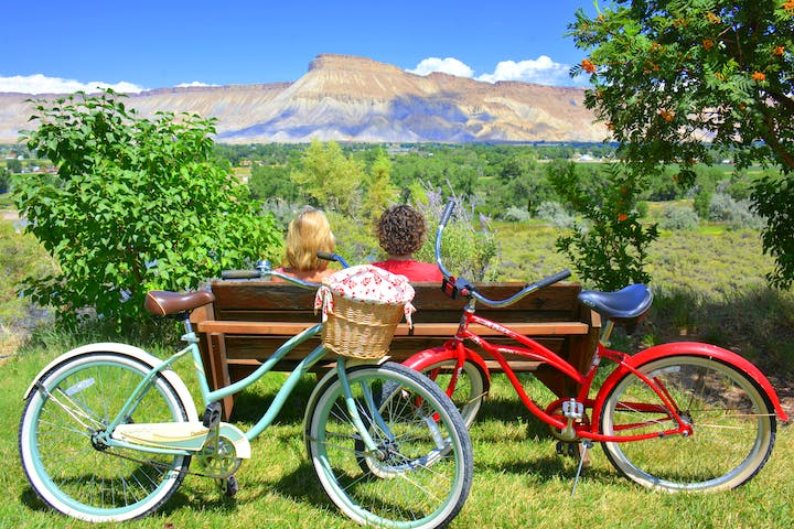 2 people on the bench with their bikes overlooking the mountains