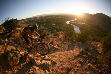 a man riding a bicycle on a dirt hill