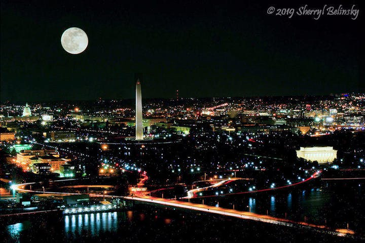 The moon over the city lights of DC