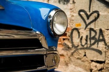 The headlight of a blue car in front of a graffitied wall