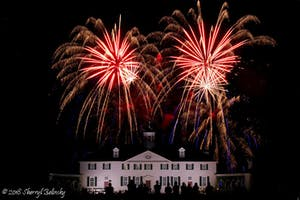Fireworks over a white mansion