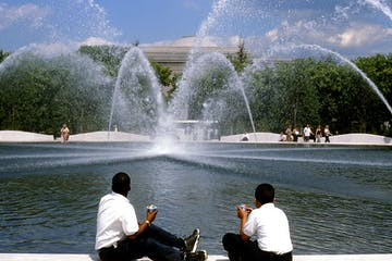 a fountain with people in front of a body of water