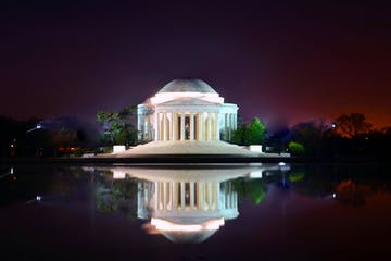 a lit up city at night with Jefferson Memorial in the background