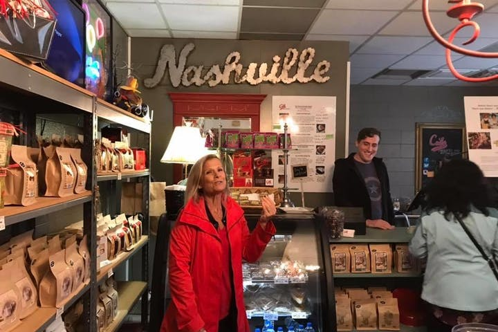 Lady in a red coat eyeing chocolates at Colt's Chocolates