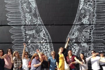 People enjoying a mural of intricate white outlined wings on a black wall