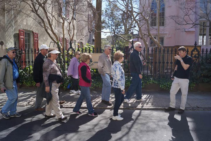 group of tourists walking through the town at daytime