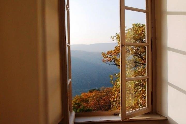 Offenes Fenster mit Ausblick auf Berge