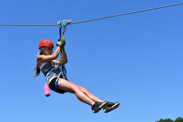 Girl using the braking system on a ziplinie above the trees