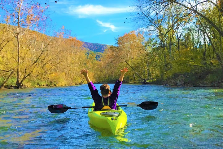 A kayaker on the river with hands raised in excitement