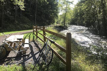 Two bikes resting by a picnic bench along the scenic trail