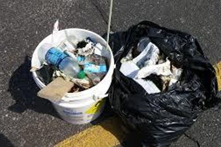 A bucket and bag full of litter collected from the river