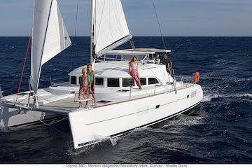 White catamaran out on water with people standing on deck