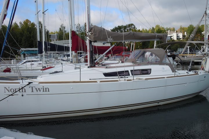 Side view of North Twin sailboat sitting in water