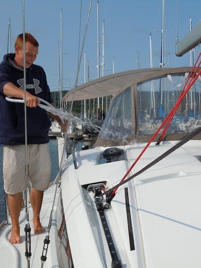 Crew member hosing off sailboat exterior