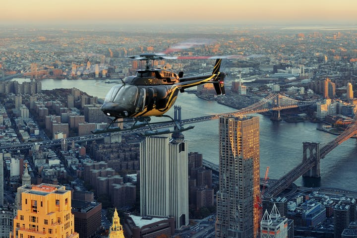 front view of helicopter flying over city and water with bridge