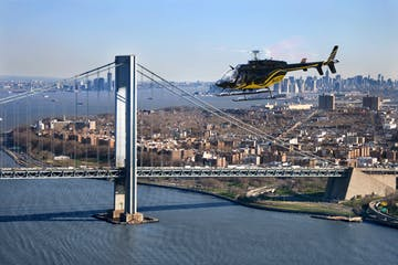 helicopter flying over water with bridge and NYC in background