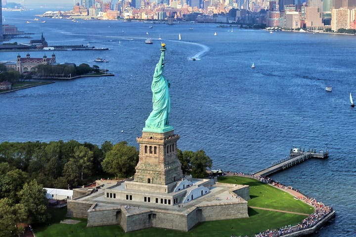 aerial view of statue of liberty on water with new york city in background