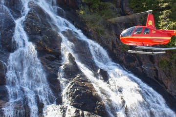 A red helicopter flying near a waterfall.