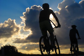 A man riding a bike during the sunset