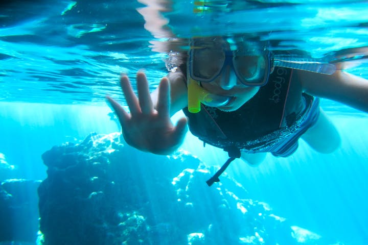 A little girl waves at the camera as she is snorkeling