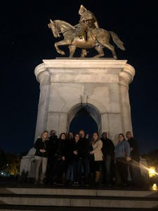 a group of people standing in front of a statue