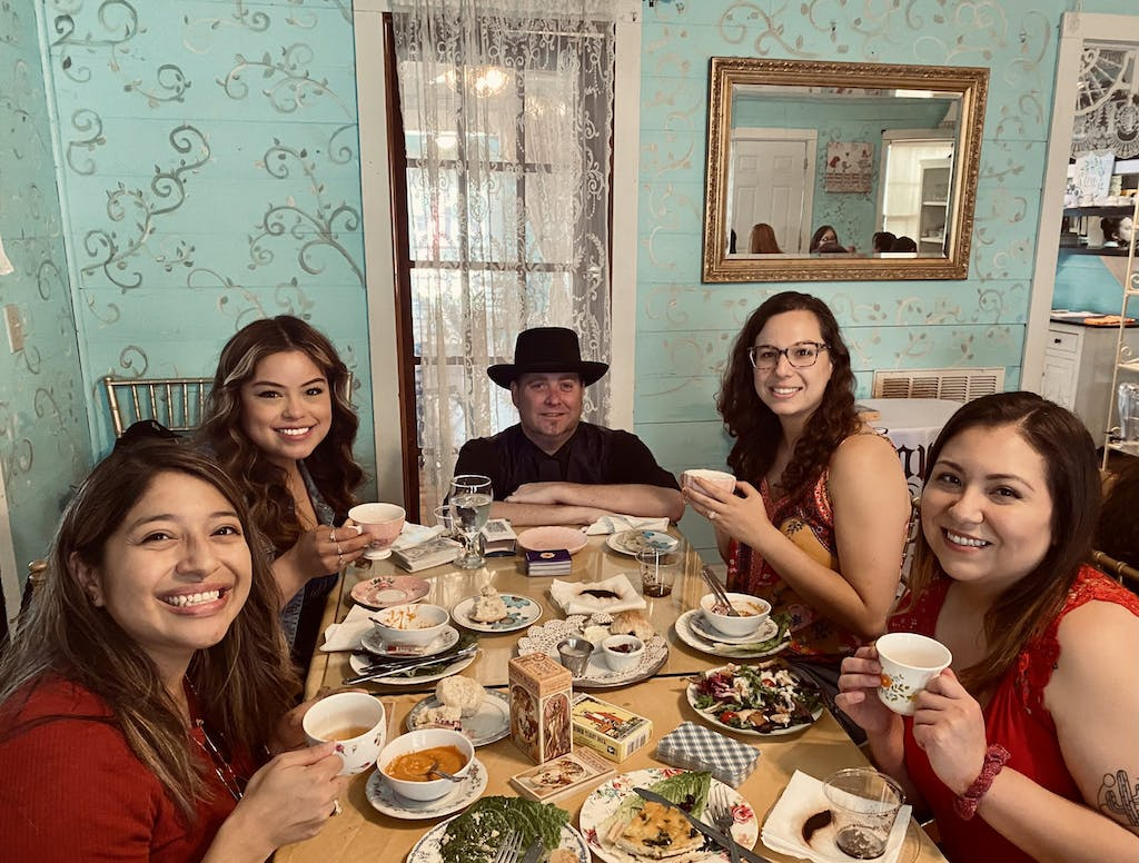 a group of people sitting at a dinner table posing for the camera