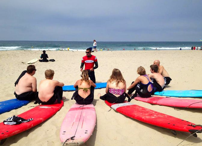 Surfari instructor with students on the beach