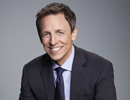 Seth Meyers wearing a suit and tie smiling at the camera