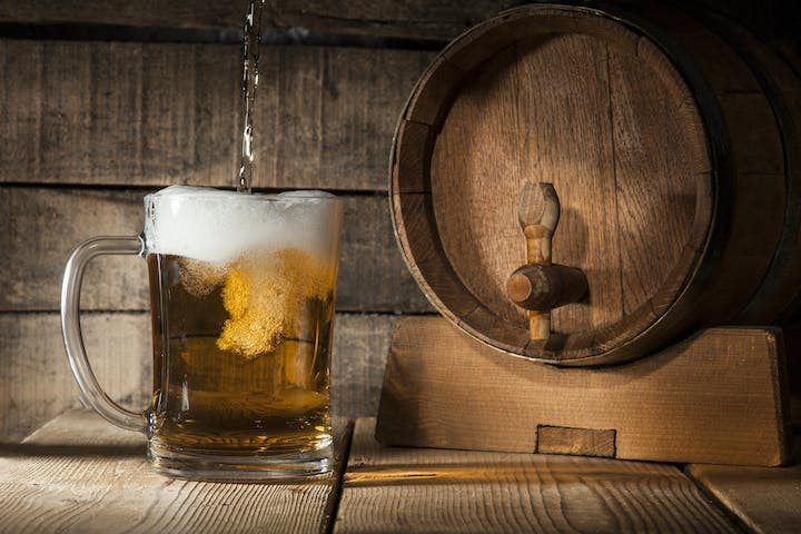 Beer barrel with beer mug on a wooden dark background