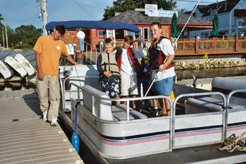 Group of adults and kids about to launch pontoon boat for a fishing camp