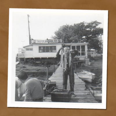 Black and white photo of man standing on dock holding up string of fish