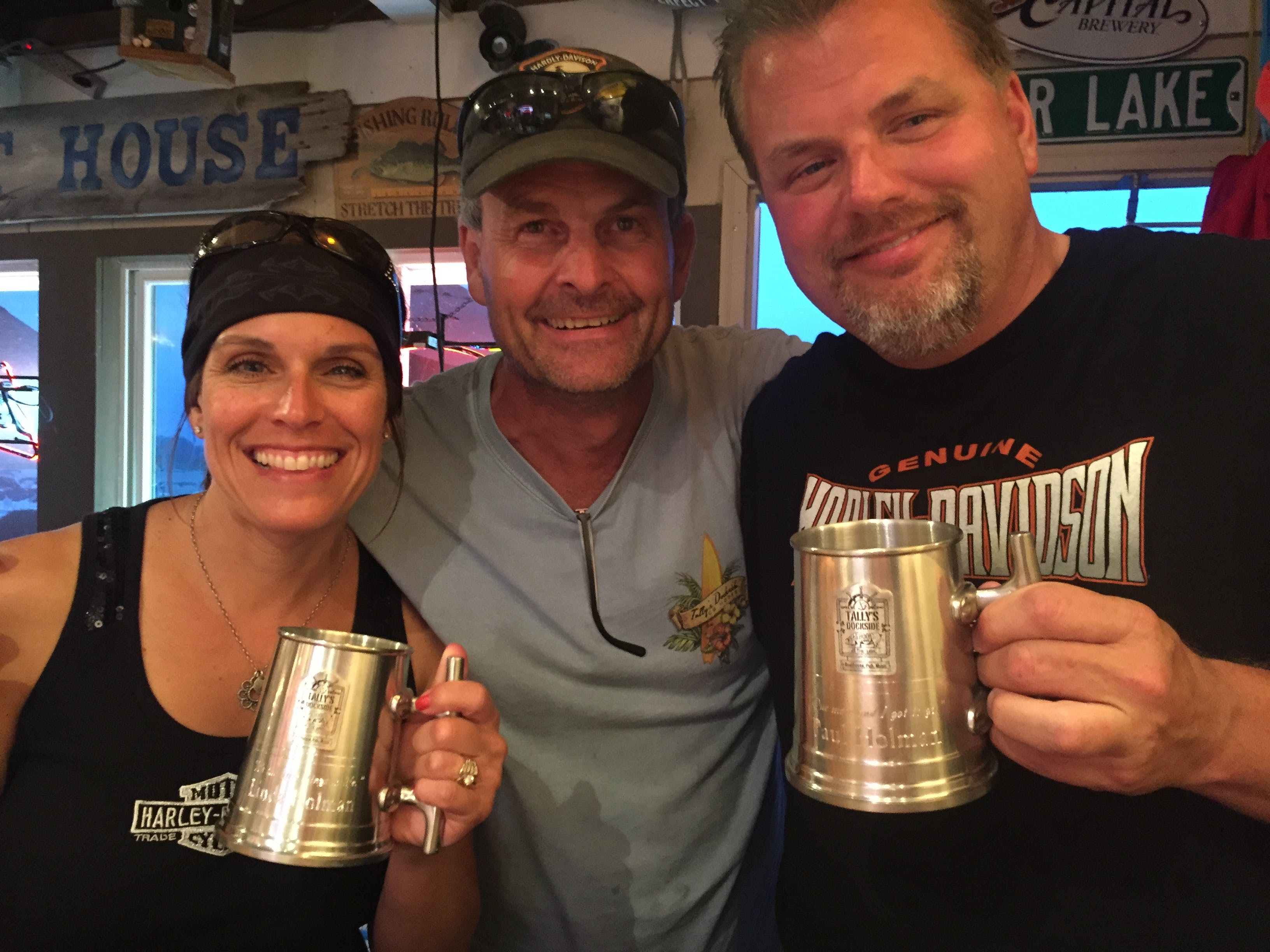 Three people holding up beer mugs and smiling at camera
