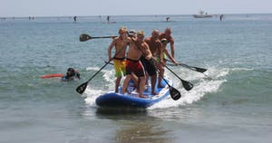 Group of people all standing on stand up paddle board paddling into shore