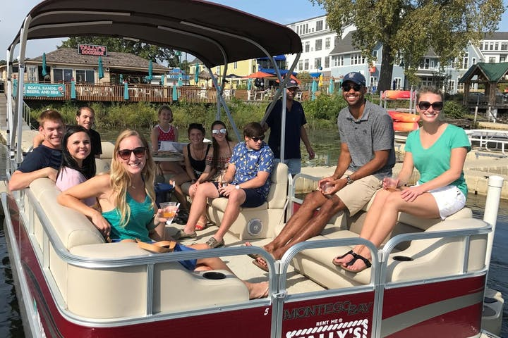 Group of people sitting in red pontoon boat