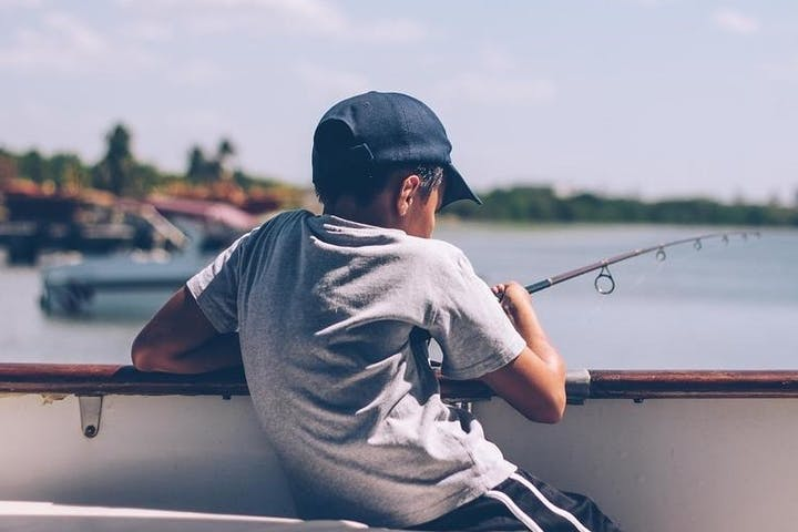 Boy reeling in fish from side of boat