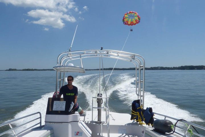A boat pulling a rainbow parasail