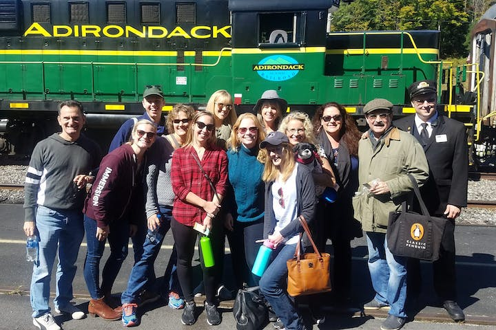 group of people outside green train