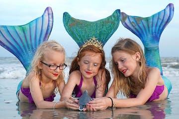 3 girls on the beach dressed as mermaids