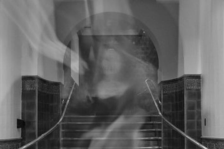 Black and white image of a ghost in front of a staircase