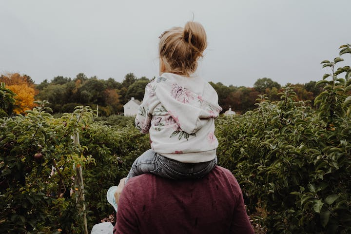 daughter on father's shoulders