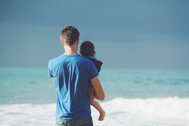 father holding daughter on beach