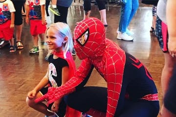 little girl posing for picture with spiderman