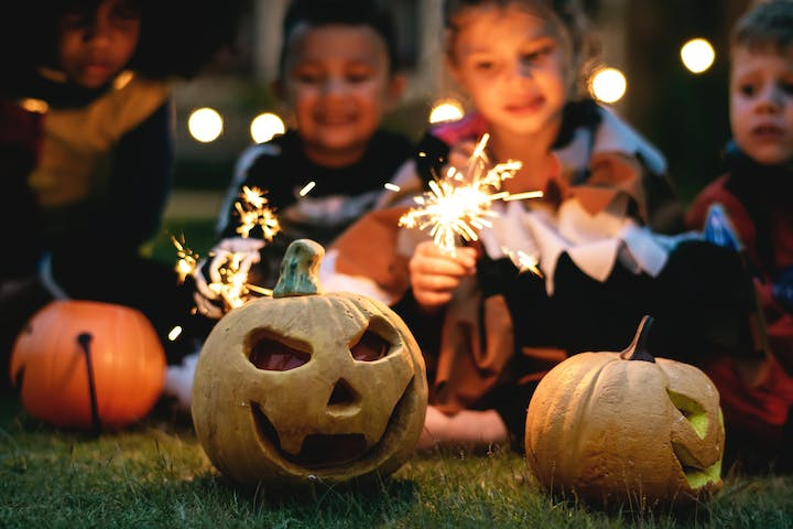 kids with sparklers and jack-o-lanterns