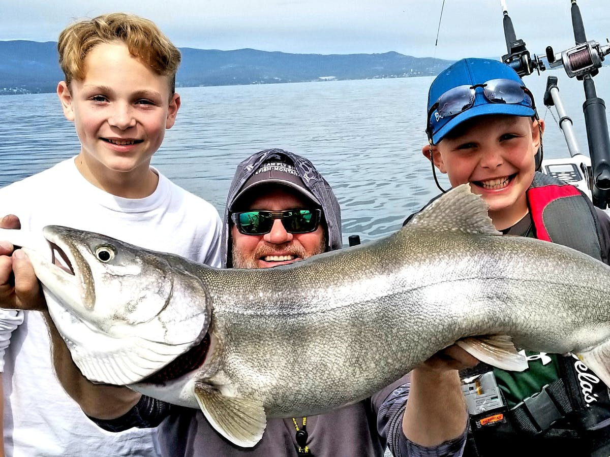 A man and 2 boys holding a fish