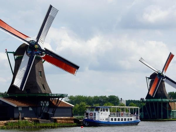 The boat on a river next to two big windmills